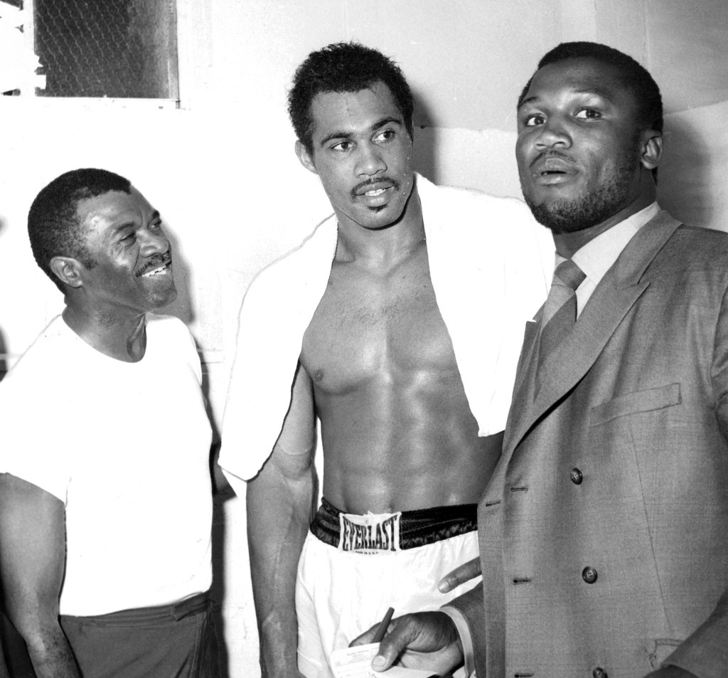 A young Norton (center) with his trainer Eddie Futch (left) and Joe Frazier.
