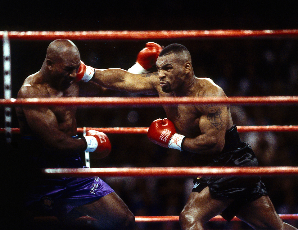Tyson charges Holyfield at the opening bell.