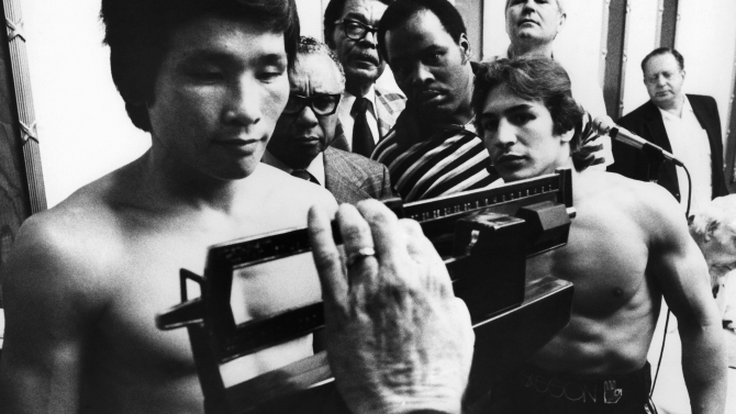 Ray Mancini watches on as challenger Duk Koo Kim weighs in for their championship fight in Las Vegas, Nov. 12, 1982.