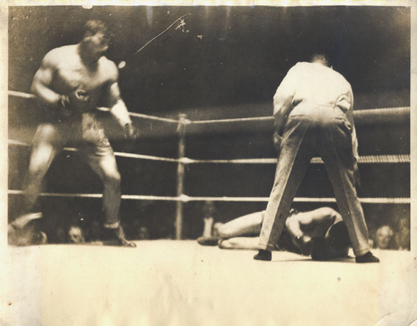 A hulking Primo Carnera stands over Stribling in the third round of their 1929 clash, which likely was not on the level.