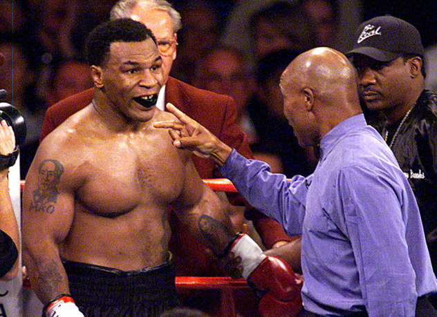 Tyson chastised by the ref after flooring Norris.