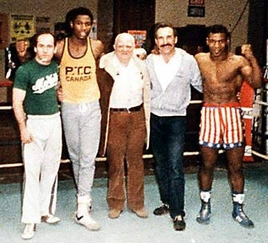 1983: Lewis second from left; Cus D'Amato center; Tyson far right.