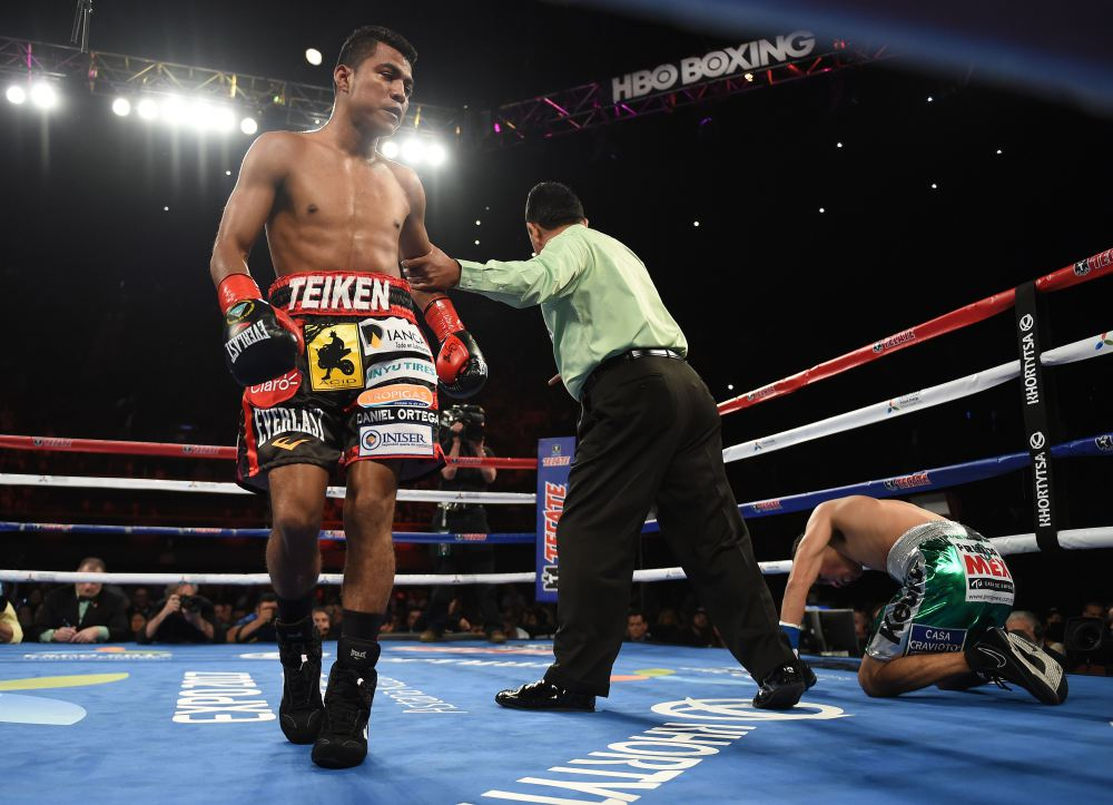 Boxer Roman Gonzalez of Nicaragua (L) knocks down Edgar Sosa of Mexico before finally knocking him out in the second round of their WBC Flyweight World Championship boxing bout at the Forum Arena in Los Angeles, California on May 16, 2015. AFP PHOTO / MARK RALSTONMARK RALSTON/AFP/Getty Images ORG XMIT: 543706011 ORIG FILE ID: 540764704