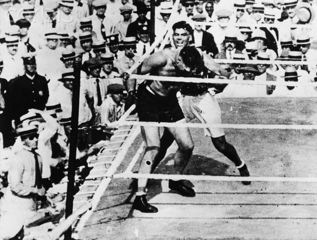 Defending champion Jess Willard reels from Dempsey's ferocious attack.