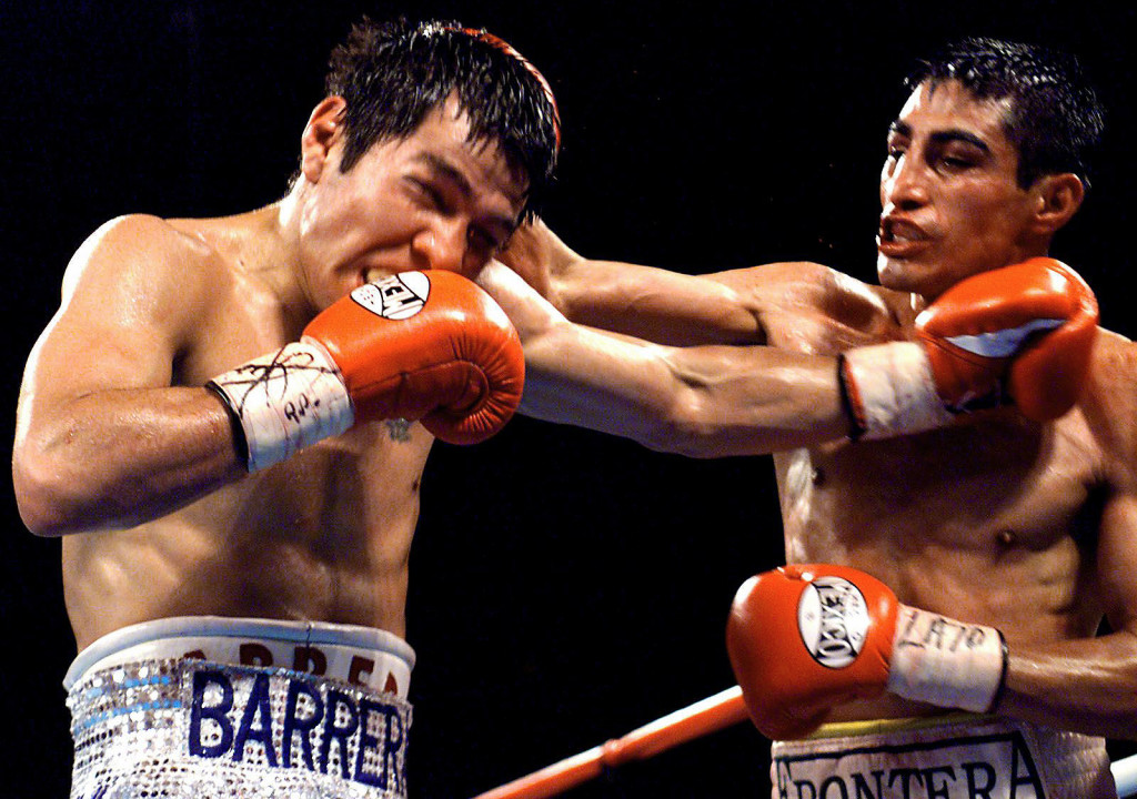 LAS VEGAS, : WBC Super Bantamweight Champion Erik Morales of Tijuana, Mexico, lands a right to the head of WBO Super Welterweight Champion Marco Antonio Barrera, of Mexico City, Mexico, late 19 February, 2000 at the Mandalay Bay Hotel in Las Vegas, NV. Morales won a 12 round split decision over Barrera to unify the two titles. AFP PHOTO John Gurzinski (Photo credit should read JOHN GURZINSKI/AFP/Getty Images)