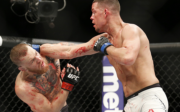 Conor McGregor, left, trades punches with Nate Diaz during their UFC 196 welterweight mixed martial arts match, Saturday, March 5, 2016, in Las Vegas. (AP Photo/Eric Jamison)